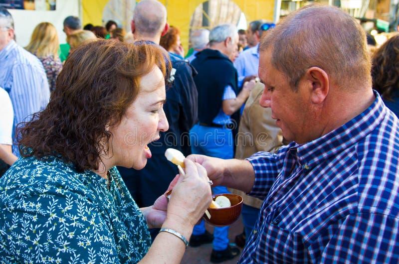 A mulher abriu sua boca O homem está alimentando um fondue de queijo da mulher com uma colher O branco derreteu estiramentos do q foto de stock royalty free