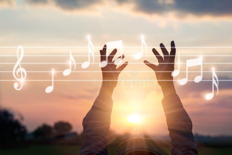 A mulher abstrata entrega notas tocantes da música no fundo da natureza, foto de stock royalty free
