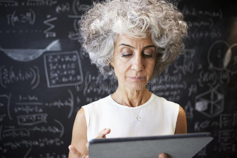 Mulher acadêmico envelhecida meio que usa a tabuleta, fim acima fotos de stock royalty free