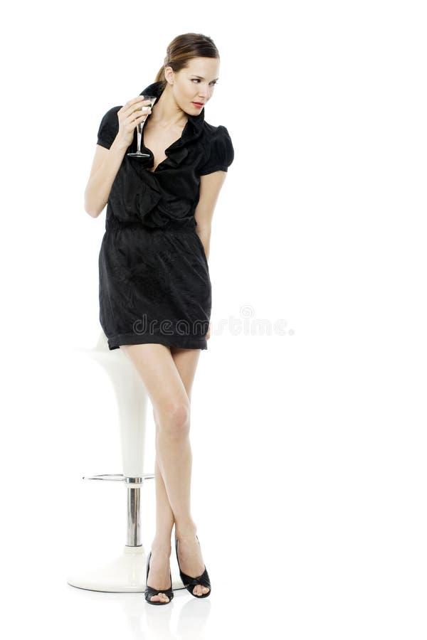Mulher acima vestida que bebe um cocktail fotografia de stock