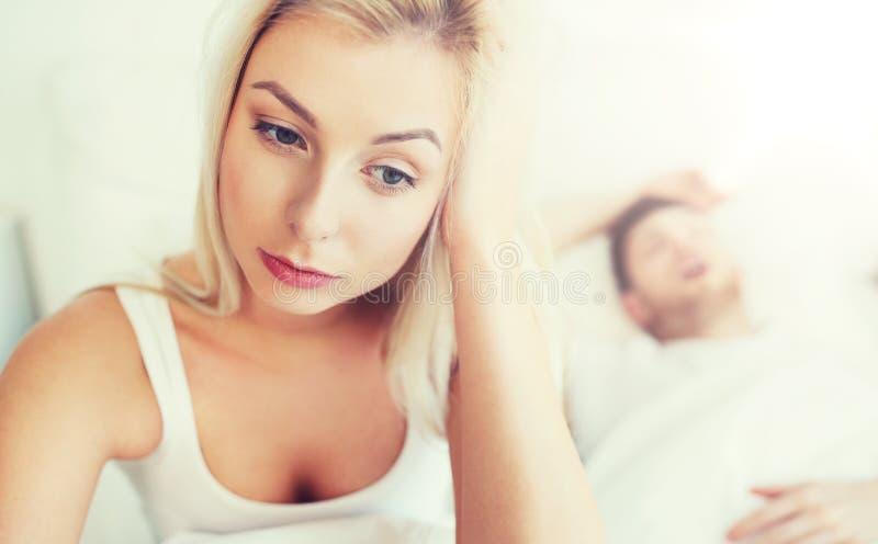 Mulher acordada que tem a insônia na cama fotografia de stock