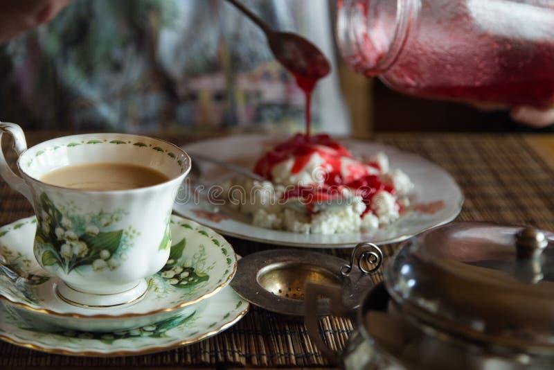A mulher adiciona o doce ao requeijão Chá com leite fotos de stock royalty free