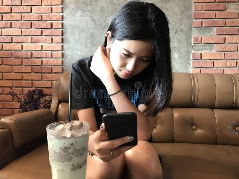 Mulher adolescente bonito asiática que joga o telefone esperto fotografia de stock