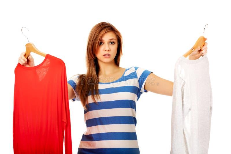 Mulher adolescente com duas camisas que pensa que vestir-se fotografia de stock royalty free