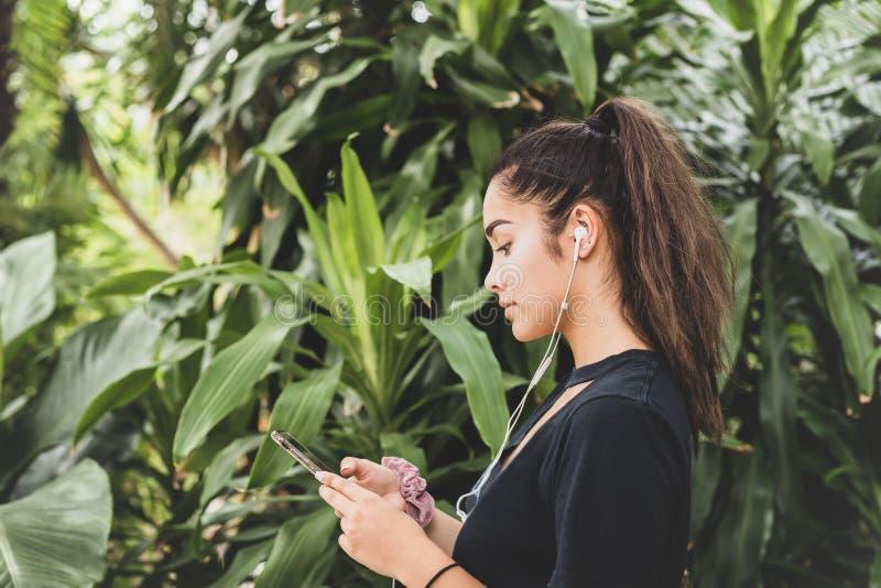 Mulher adolescente da raça misturada com fones de ouvido que escuta a música, contra o fundo tropical das árvores verdes fotografia de stock royalty free