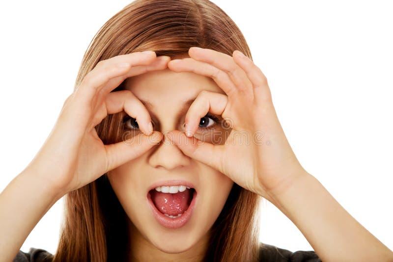 Mulher adolescente que faz as mãos dos binóculos fotografia de stock royalty free