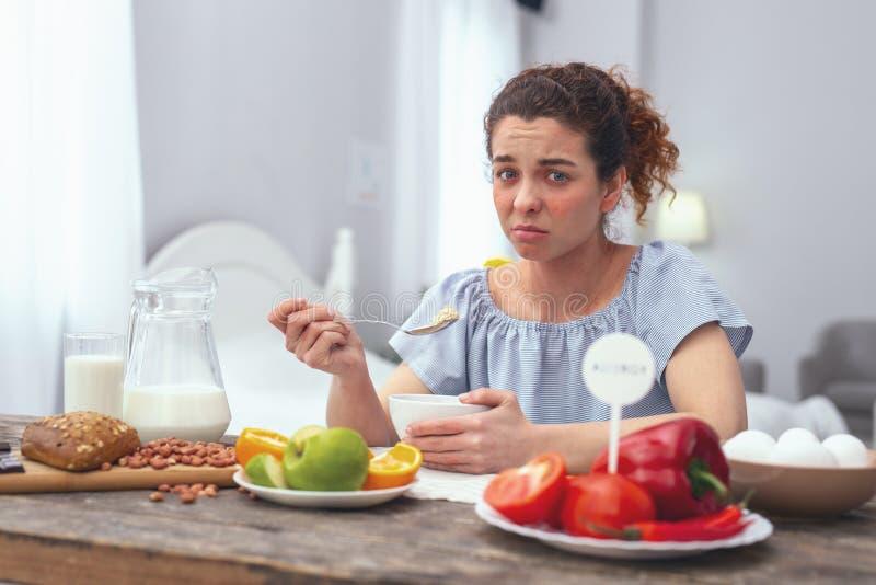 A mulher adolescente que tem que comer saudável devido ao estômago virado foto de stock