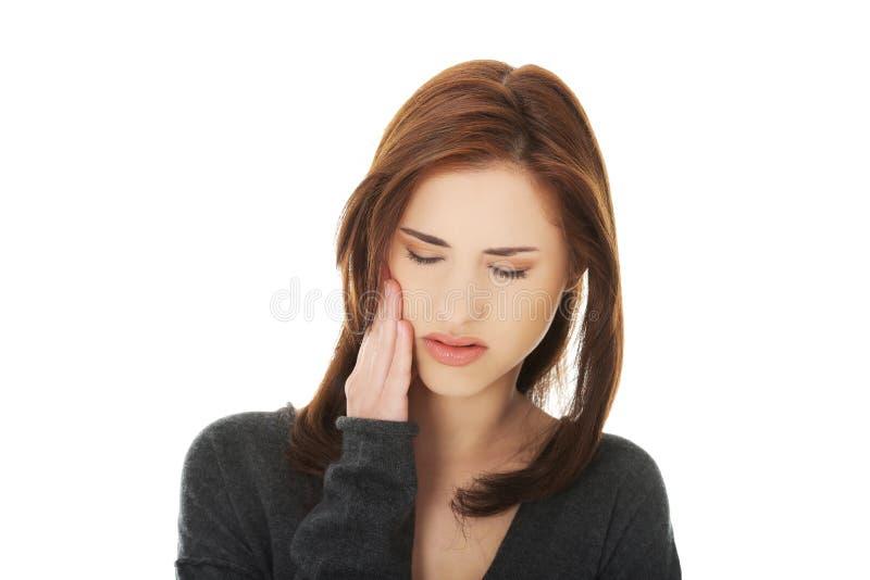 Mulher adolescente que tem uma dor terrível do dente imagem de stock