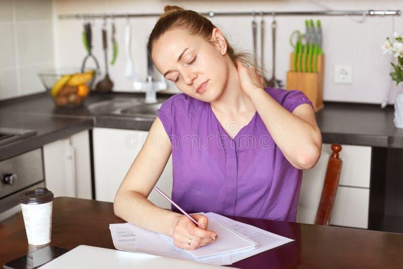 A mulher adorável da fadiga tem a dor no pescoço, sendo sobrecarregado, escreve nos papéis, senta-se contra o inerior da cozinha  imagens de stock royalty free