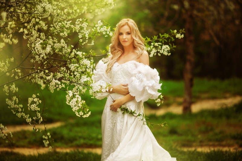 Mulher adorável despreocupada de salto cândido no campo com as flores no por do sol do verão foto de stock
