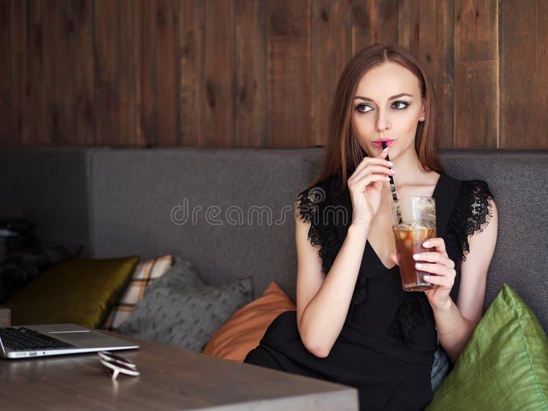 Mulher adorável nova com composição na moda dos olhos lindos e o equipamento à moda que bebe a xícara de café de vidro grande com fotografia de stock