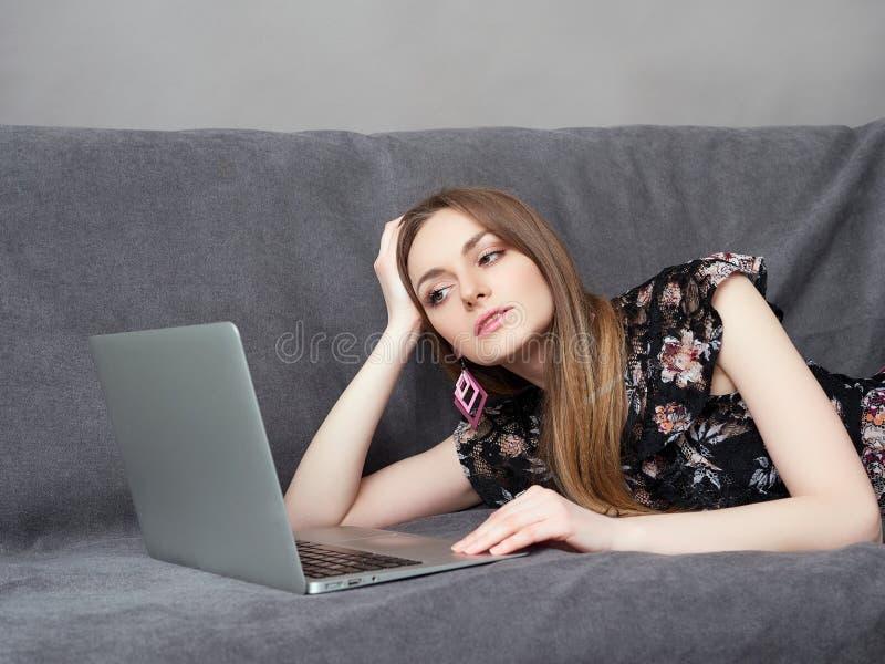 A mulher adorável nova feliz no vestido longo encontra-se no sofá cinzento com portátil em casa contra a parede cinzenta foto de stock