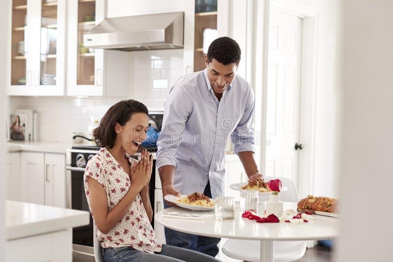 Mulher adulta afro-americano nova que senta-se na tabela na cozinha, seu sócio surpreendente ela servindo uma refeição romântica, fotografia de stock