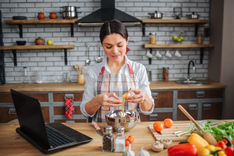 A mulher adulta agradável senta-se na tabela na cozinha Quebra ovos e derrama-os na bacia Olhar modelo para baixo Concentrou-se fotografia de stock
