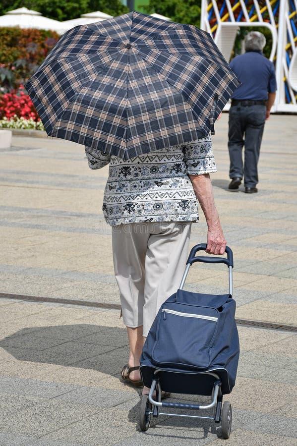A mulher adulta anda com um carrinho de compras fotos de stock royalty free
