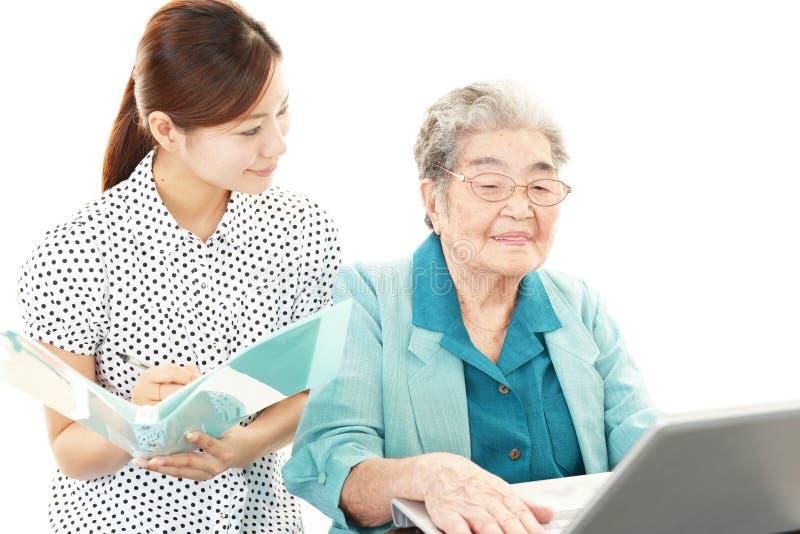 A mulher adulta aprecia o laptop foto de stock royalty free
