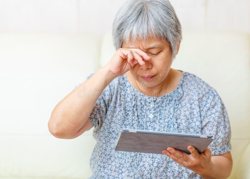 Mulher adulta asiática que usa a tabuleta digital imagens de stock royalty free