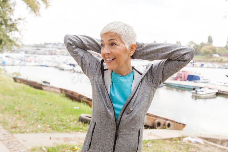 Mulher adulta ativa de sorriso que faz o exercício da aptidão fotos de stock