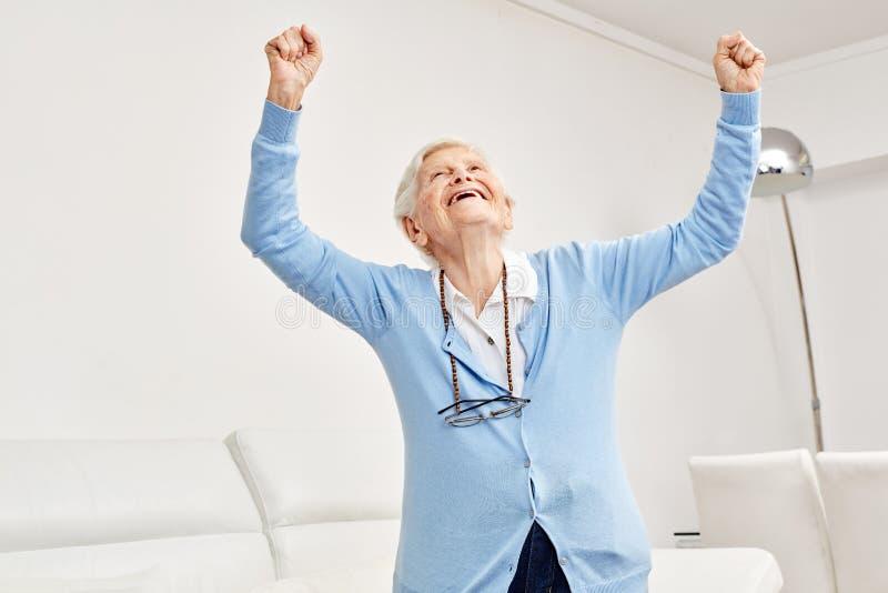 A mulher adulta aumenta entusiasticamente ambos os punhos imagem de stock royalty free