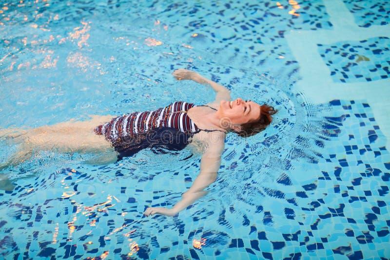 Mulher adulta bonita em natação listrada do roupa de banho na associação azul nela para trás no recurso Conceito da saúde da ativ imagens de stock