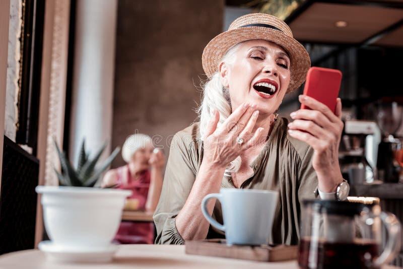 Mulher adulta bonita excitada que ri ao ter a conversação imagem de stock royalty free