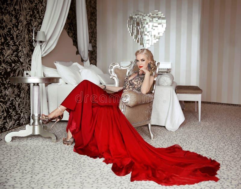 Mulher adulta bonita no vestido vermelho da forma que senta-se no braço moderno imagens de stock royalty free