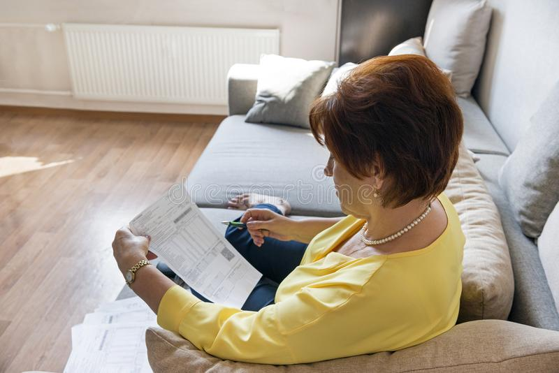 Mulher adulta branca que considera contas no sofá, mulher com bi imagem de stock royalty free