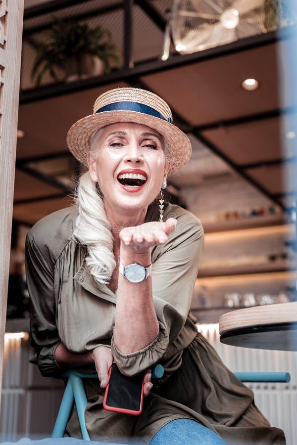 Mulher adulta brilhante alegre que veste o equipamento à moda ao sentar-se em um café foto de stock
