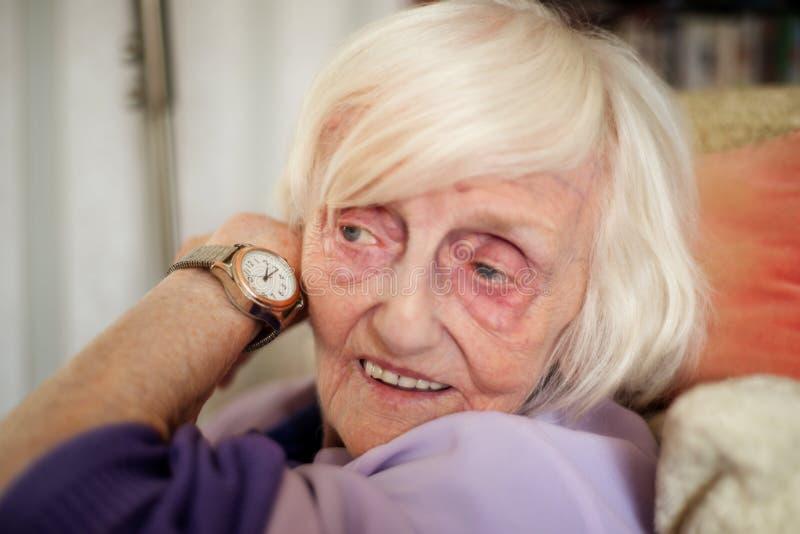 A mulher adulta cega escuta o tempo em seu relógio de pulso falador foto de stock