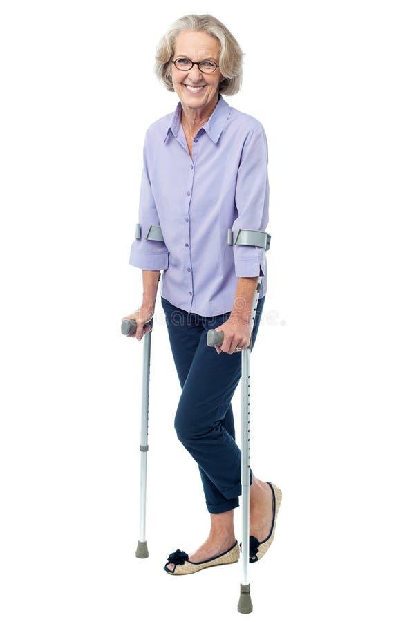 Mulher adulta com óculos que anda com muletas fotos de stock royalty free