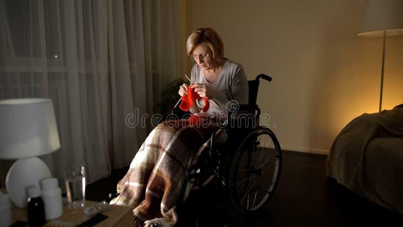 Mulher adulta com a doença de Parkinson que tenta fazer malha, noite triste no lar de idosos imagens de stock royalty free