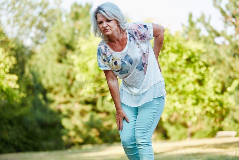 Mulher adulta com dor do lumbago foto de stock