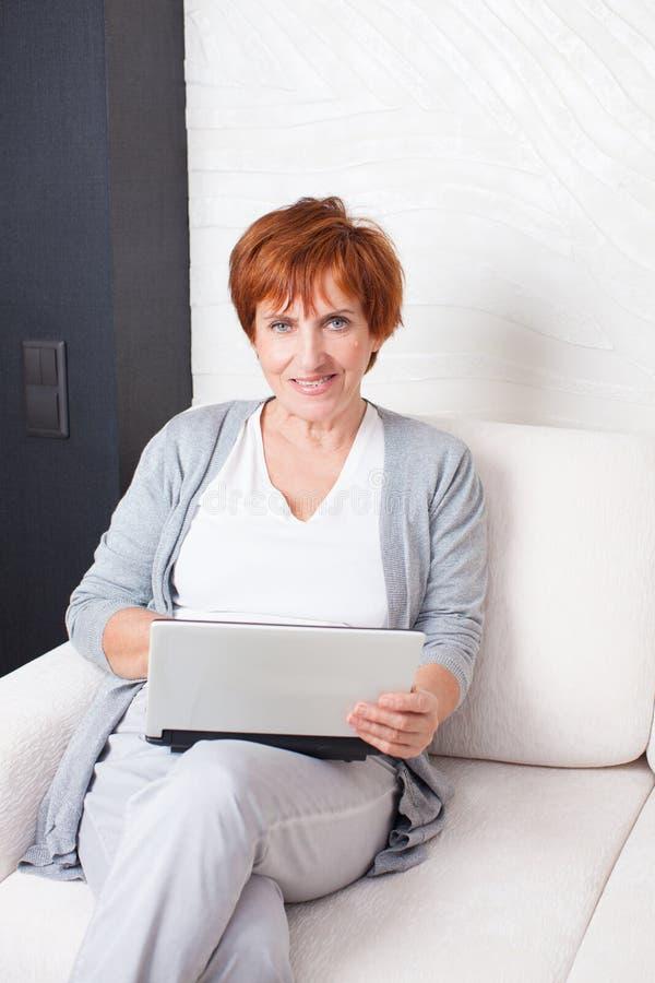 Mulher adulta com portátil em casa imagens de stock