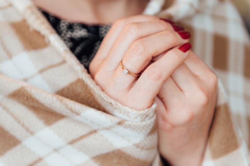 A mulher adulta com um anel em sua mão escondeu a manta fotografia de stock