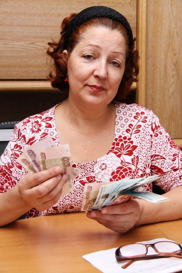 A mulher adulta conta o dinheiro imagem de stock royalty free