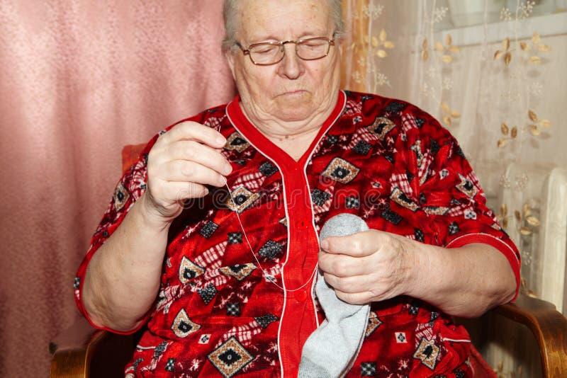 Mulher adulta a costurar sobre um rasgo fotografia de stock