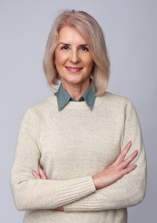 Mulher adulta de sorriso isolada no cinza imagens de stock