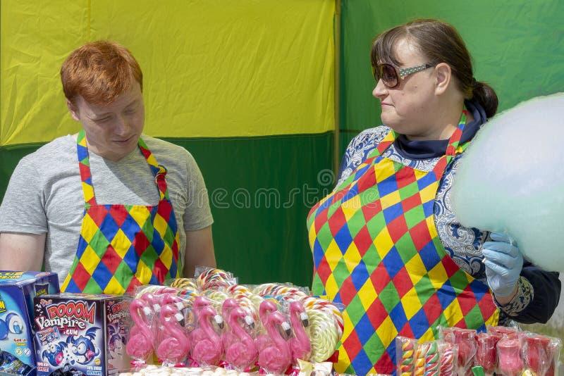 Mulher adulta e homem novo atrás do sweetsd contrário da venda fotos de stock royalty free