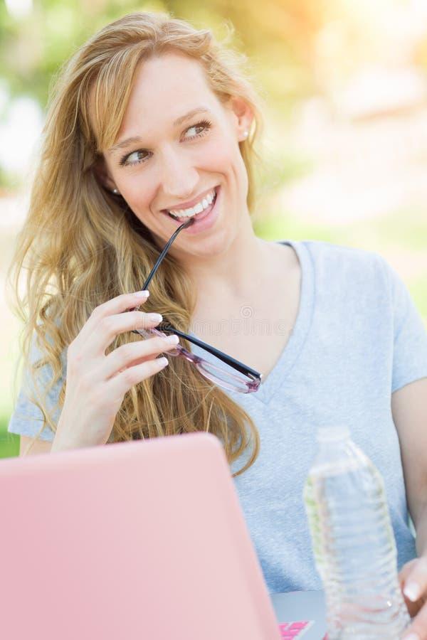 Mulher adulta entusiasmado com os vidros que usam fora seu portátil imagens de stock