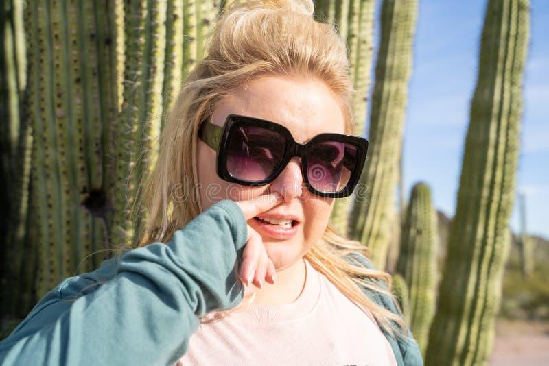 A mulher adulta escolhe seu nariz no deserto, ao lado de um cacto gigante da tubulação de órgão no Arizona fotos de stock