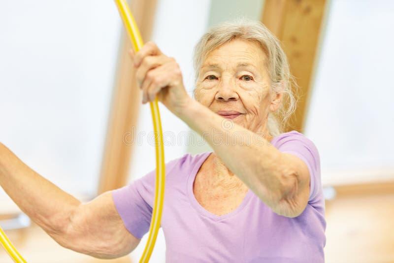 A mulher adulta está fazendo um exercício com o pneu imagens de stock
