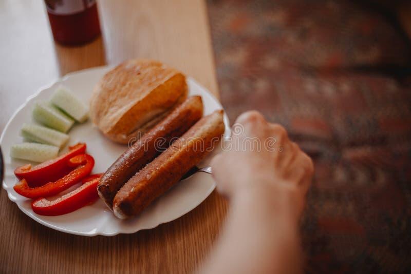 A mulher adulta est? cozinhando alguma bratwurst foto de stock