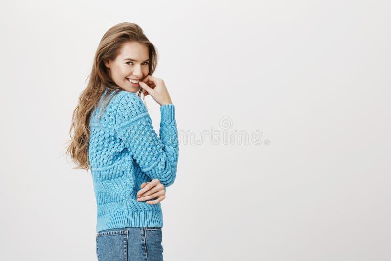 Mulher adulta europeia bonita que está no perfil ao girar na câmera, ao sorrir e ao guardar o dedo perto do bordo com fotografia de stock