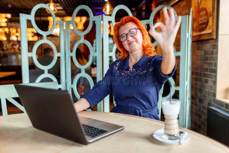 Mulher adulta feliz, sentando-se no café, sorrindo e mostrando a aprovação do gesto Dentro no café imagens de stock royalty free