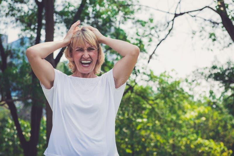 A mulher adulta fica com raiva e gritando no parque fotografia de stock royalty free