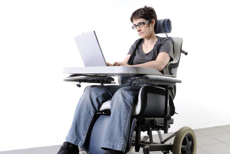 Mulher adulta incapacitada com portátil em uma cadeira de rodas