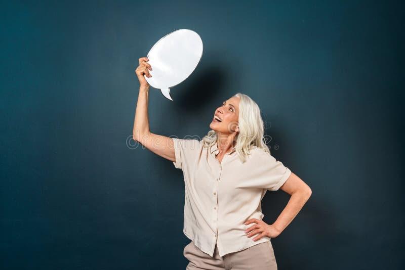 Mulher adulta madura alegre que guarda a bolha do discurso fotografia de stock royalty free