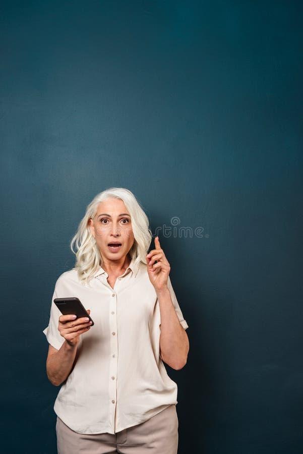 Mulher adulta madura chocada entusiasmado que usa o telefone celular imagem de stock