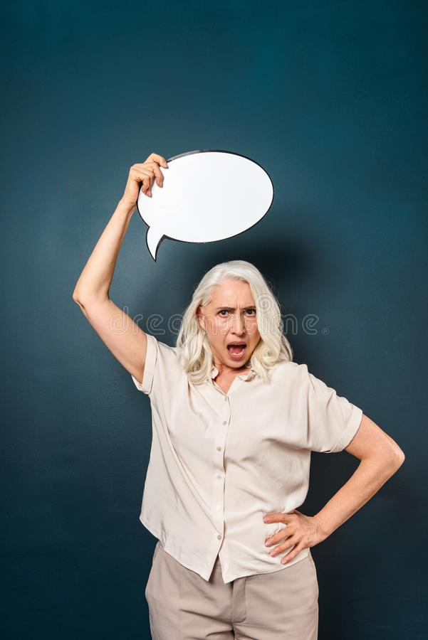Mulher adulta madura desagradada que guarda a bolha do discurso fotos de stock