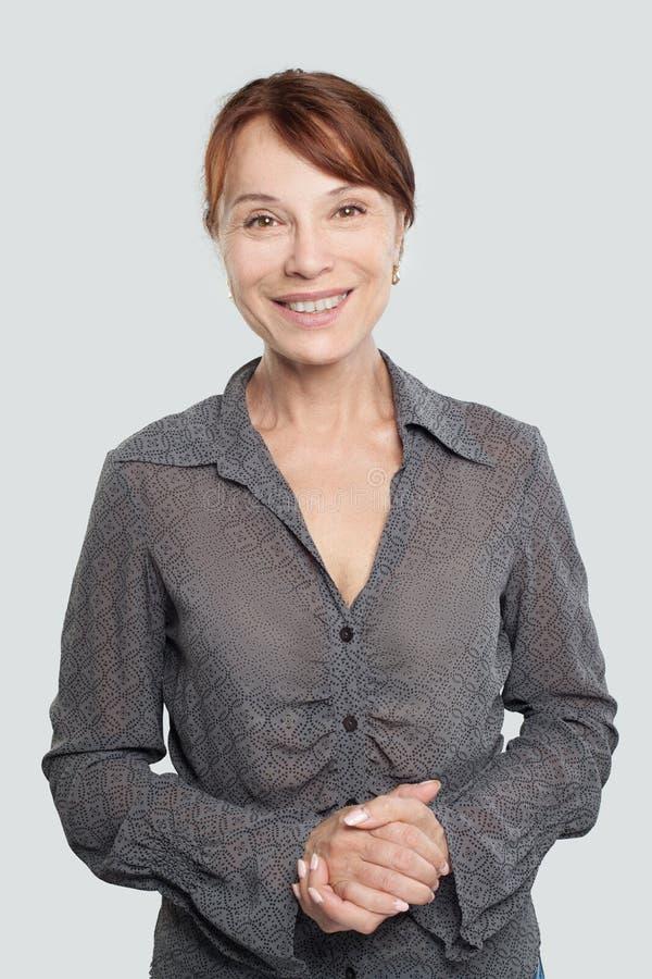 Mulher adulta meados de feliz no fundo branco fotografia de stock